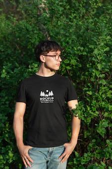 自然の中でモックアップtシャツを着ている若い男