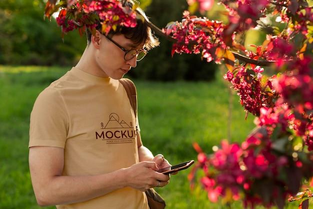 밖에서 모형 티셔츠를 입은 청년