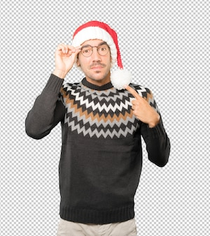 Young man wearing a christmas hat while gesturing isolated