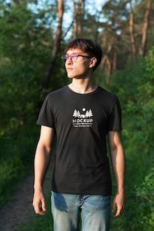 一个穿着模拟t恤的年轻人在森林里