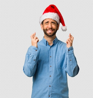 Young man wearing santa hat crossing fingers for having luck