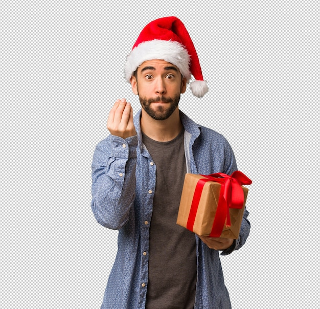 Young man wearing santa hat doing a typical italian gesture