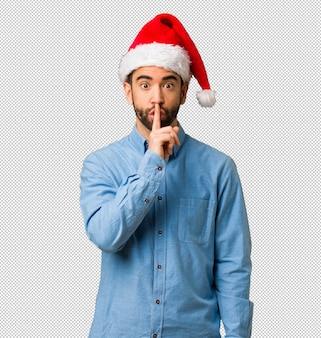 秘密を保つ、または沈黙を求めるサンタの帽子を身に着けている若い男