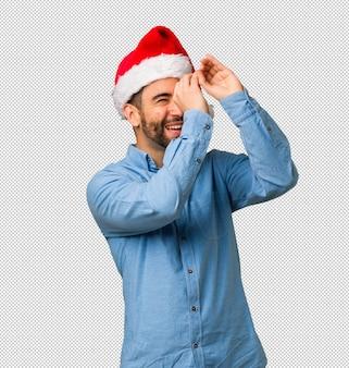 망원경의 제스처를 만드는 산타 모자를 쓰고 젊은 남자