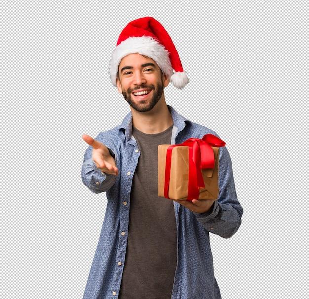 Young man wearing santa hat reaching out to greet someone