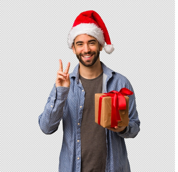 Young man wearing santa hat showing number two