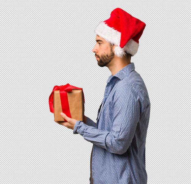 Young man wearing santa hat on the side looking to front