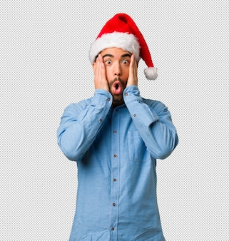 Young man wearing santa hat surprised and shocked
