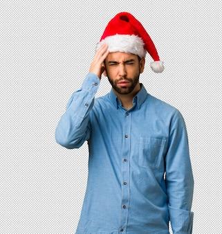 疲れて、非常に眠いサンタの帽子を身に着けている若い男