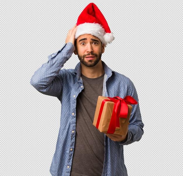 걱정과 압도 산타 모자를 쓰고 젊은 남자