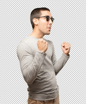 Young man wearing sunglasses and doing gestures