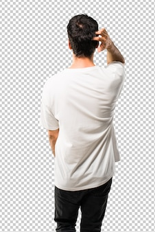 Young man with white shirt on back position looking back while scratching head