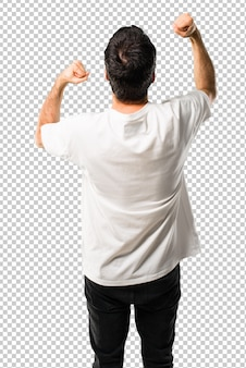 Young man with white shirt celebrating a victory and surprised to be successful