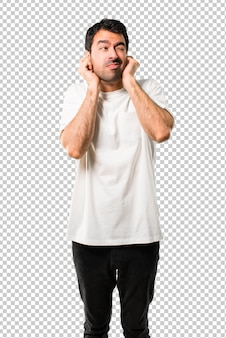 Young man with white shirt covering both ears with hands. frustrated expression