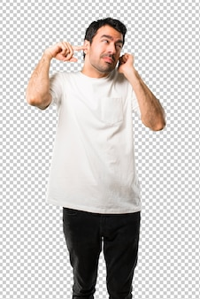 Young man with white shirt covering both ears with hands
