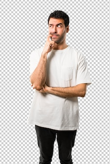 Young man with white shirt having doubts and with confuse face expression while looking up