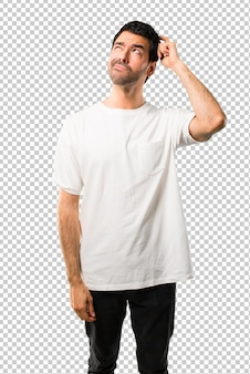 Young man with white shirt having doubts and with confuse face expression while scratching head