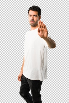 Young man with white shirt making stop gesture with her hand denying a situation that thinks wrong