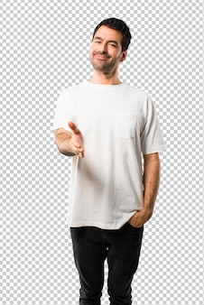 Молодой человек с белой рубашкой пожимает руку за заключение хорошей сделки