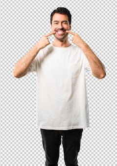 Молодой человек с белой рубашкой, улыбаясь со счастливым и приятным выражением, указывая мо