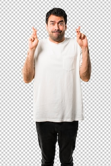 Young man with white shirt with fingers crossing and wishing the best. making a wish.
