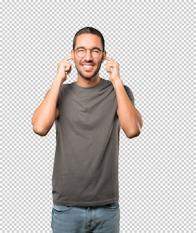 Young man worried about loud noises and covering his ears