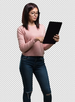 Young pretty woman smiling and confident, holding a tablet, using it to surf the internet and see social networks, communication