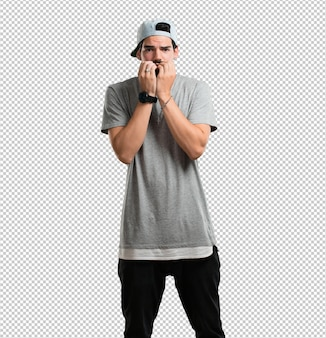 Young rapper man biting nails, nervous and very anxious and scared for the future
