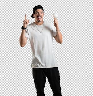 아이디어, 상상력, 정신적 유동성과 지혜, 영감의 상징으로 전구를 들고 위쪽을 가리키는 쾌활하고 흥분 젊은 랩퍼 남자 photo