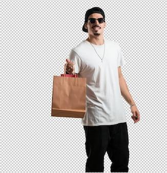 젊은 랩퍼 남자가 명랑하고 웃고, 쇼핑백을 들고 매우 흥분
