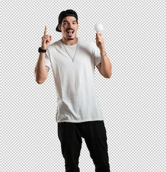 Young rapper man cheerful and excited, pointing upwards, holding a light bulb as a symbol of idea, imagination, mental fluidity and wisdom, inspirational photo