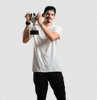 Young rapper man excited and energetic, raising a glass after having achieved a difficult victory, reward for hard work, confident and positive