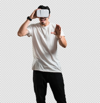 Young rapper man excited and entertained, playing with virtual reality glasses, exploring a fantasy world, trying to touch something