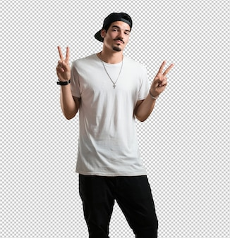 Young rapper man fun and happy, positive and natural, makes a gesture of victory