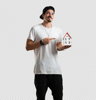 Young rapper man happy and confident, showing a miniature house model