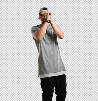 Young rapper man looking through a gap, hiding and squinting