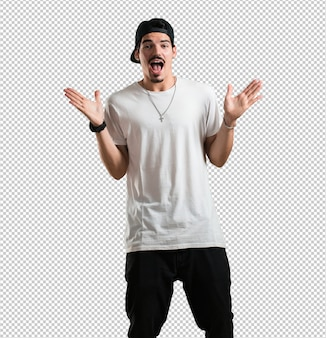 Young rapper man screaming happy, surprised by an offer or a promotion, gaping, jumping and proud