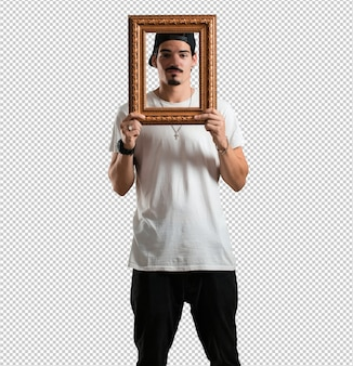 Young rapper man smiling and relaxed, looking through a frame, funny and creative photo