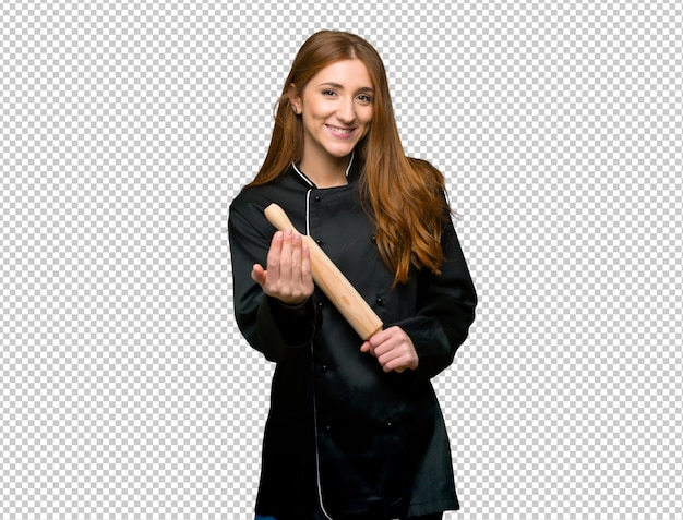 Young redhead chef woman inviting to come with hand. happy that you came