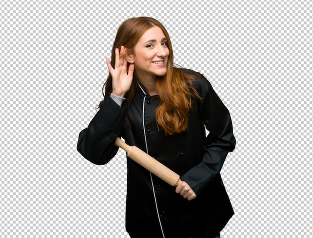 Young redhead chef woman listening to something by putting hand on the ear
