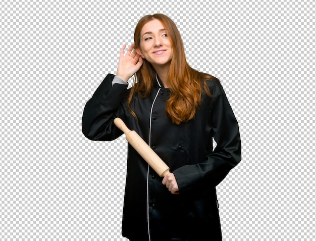 若い赤毛のシェフの女性が耳に手を置くことによって何かを聞いて