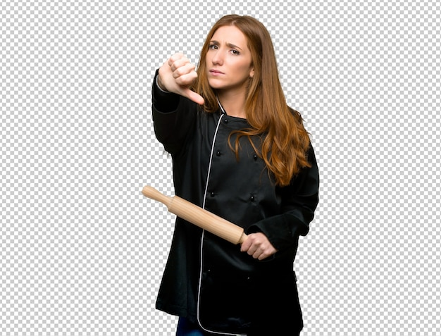 Young redhead chef woman showing thumb down sign with negative expression