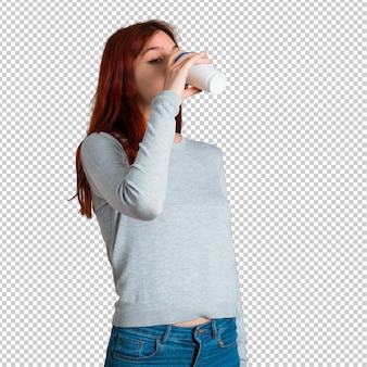 Young redhead girl drinking hot coffee in takeaway paper cup