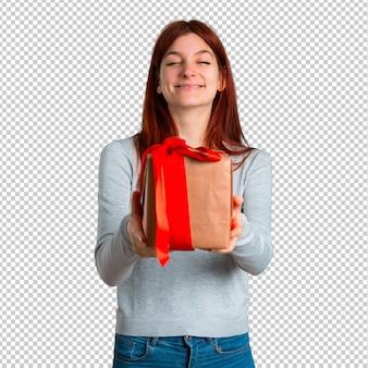 손에 선물 상자를 들고 젊은 빨강 머리 소녀