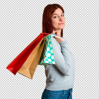 Young redhead girl holding a lot of shopping bags
