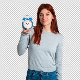 ヴィンテージの目覚まし時計を保持する若い赤毛の女