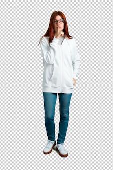 Молодая рыжая девушка в городской белой толстовке с очками, показывающая знак закрытия моу