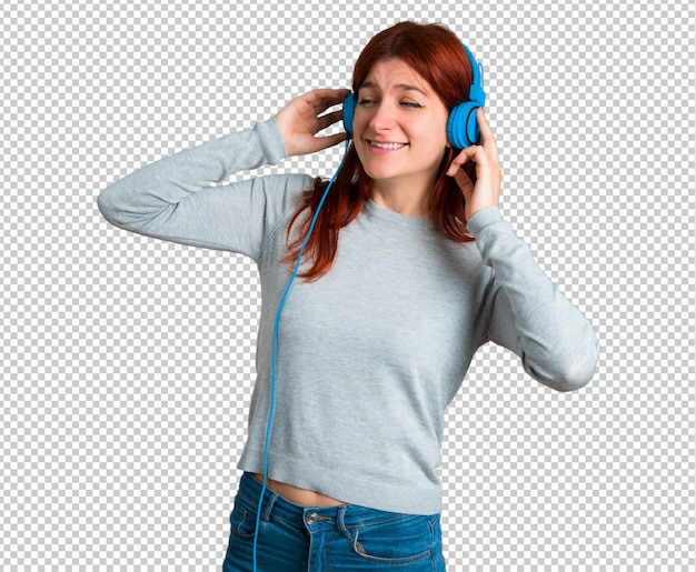 Young redhead girl listening to music with headphones