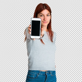Young redhead girl looking at the camera and smiling while using the mobile