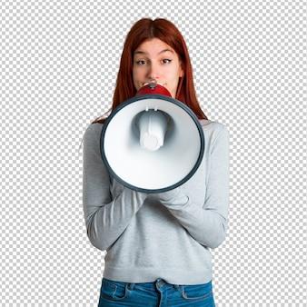 Молодая рыжая девушка кричит через мегафон, чтобы объявить что-то